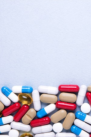 Pharmaceutical preparations, background. Colorful medications Pills, tablets and capsules are scattered. Medical concept.
