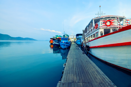 National, multi-colored tourist boats at the pier at sunset. Boat mooring in Thailand, the fishing village of Bang Bao, Koh Chang Island. Copy space