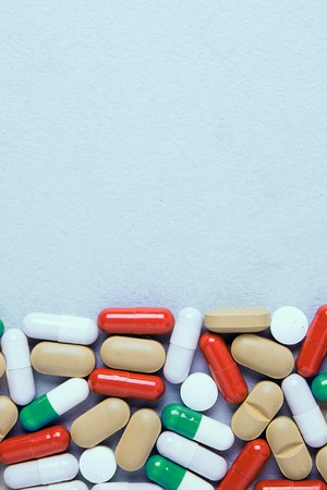 Colourful medications pills, tablets and capsules are scattered. Stock Photo