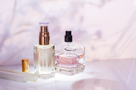 Perfume bottle on a light pink floral background. Perfumery collection Stock Photo
