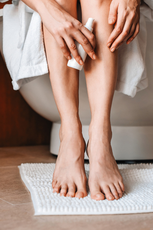 Body care. A young woman in the bathroom applies natural cream to her legs. Cosmetics and anti-cellulite care Banco de Imagens