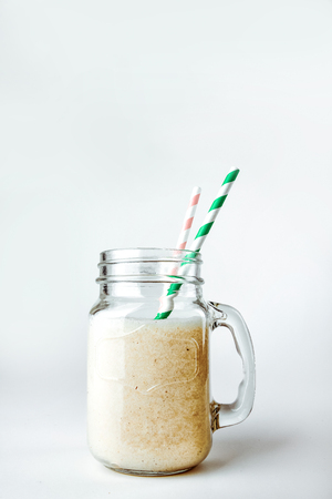 Protein cocktail with milk, vanilla in a glass jar with straws. Sports nutrition 스톡 콘텐츠