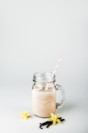 Protein cocktail with milk, vanilla in a glass jar with straws. Sports nutrition Stockfoto
