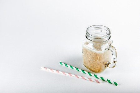 Protein cocktail, smoothie with milk, vanilla in a glass jar with straws.
