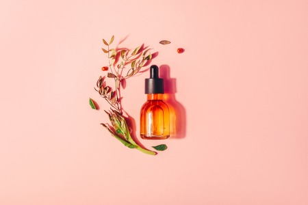 Bottle with natural serum with vitamins on a pink background. Cosmetic procedures for the face
