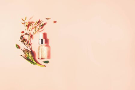 Bottle with natural serum with vitamins on a pink background. Cosmetic procedures for the face Reklamní fotografie - 124787526