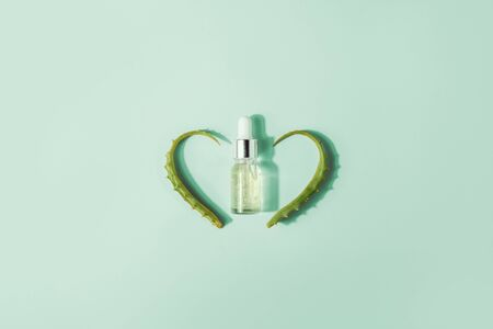 Bottle with serum, extract with aloe vera leaves. Cosmetic procedures for face and body