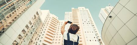 A girl is taking pictures of a new residential complex. White modern skyscrapers