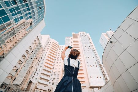 A girl is taking pictures of a new residential complex White modern skyscrapers. Reklamní fotografie