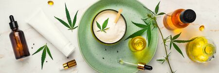 Bank of medicinal cream with CBD oil, bottle of cannabis oil, capsules, on a green plate. Flat lay, top view. Banner Stock Photo