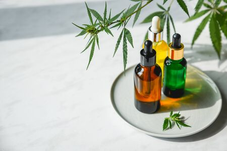 Glass bottles with CBD oil, THC tincture and hemp leaves on a marble background. Flat lay Cosmetics cannabis oil.