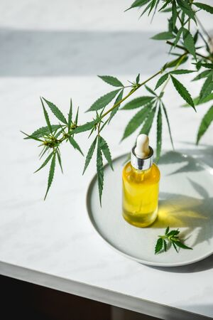 Glass bottle with cannabis oil with hemp leaves on a marble background. Copy space.