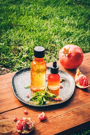 Trendy sunlight pomegranate seed oil, whey in different bottles on wooden background. Concept of anti-aging organic skin care. Ripe pomegranates lie nearby
