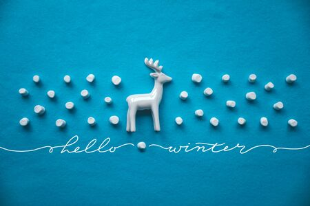 Hello winter concept. Composition with reindeer and decorative marshmallow snow on a blue background