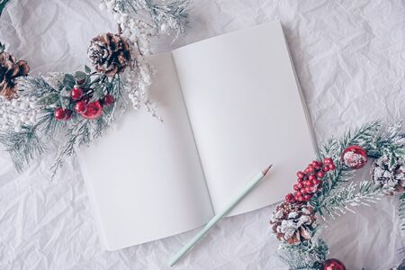 Christmas concept. White notebook with christmas decoration, wreath on a white background. Minimal winter vacation idea. Flat lay top view composition.