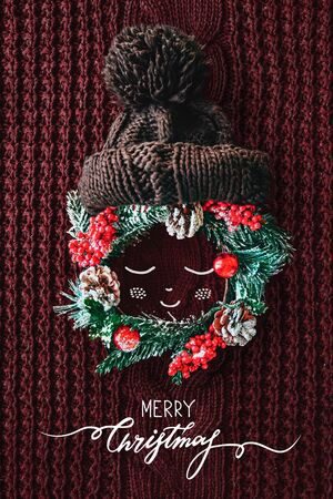 Christmas concept Cute baby made from a wreath of evergreen spruce, knitted hat and illustration on a red knitted background. Minimal winter vacation idea. Flat lay top view composition. Stockfoto