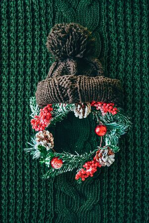 Santa claus christmas concept made of wreath of evergreen fir, knitted hat on green knitted background. Minimal winter vacation idea. Flat lay top view composition.