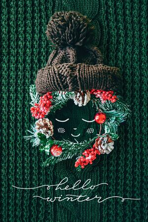 Hello Winter concept. Cute baby made of a wreath of evergreen spruce, knitted hat and illustration on a knitted green background. Minimal winter vacation idea. Flat lay top view composition.