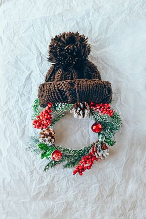 Santa claus christmas concept made of wreath of evergreen spruce, knitted hat on a white snowy background. Minimal winter vacation idea. Flat lay top view composition. Stockfoto