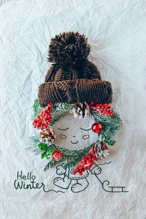Christmas concept. Cute baby made of wreath of evergreen spruce, knitted hat and illustration on a white background. Minimal winter vacation idea. Flat lay top view composition. Stockfoto