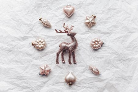 Creative composition with Cerulen deer and Christmas wreath, circle of decorative ornaments. Flat lay, pastel. Minimalism.