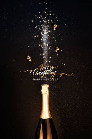 Festive Christmas background. Bottle of champagne with a spray of sparkles and Christmas decorations. Happy new year concept Foto de archivo