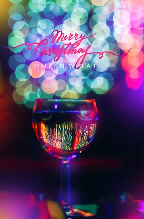 Holiday background. A glass of wine, champagne on a background of bright multi-colored bokeh. The concept of a solemn feast, congratulations