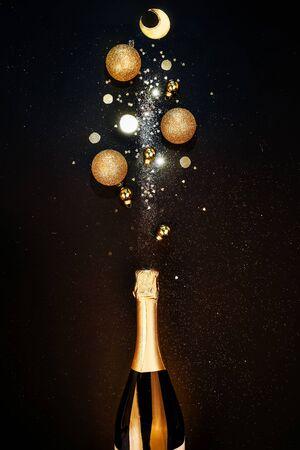Fondo festivo de Navidad. Botella de champagne con spray de destellos y adornos navideños. Feliz año nuevo concepto Foto de archivo