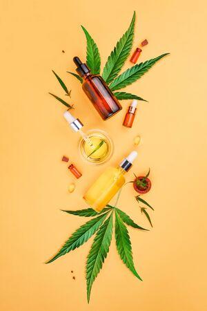 Glass bottles with CBD oil, THC tincture and hemp leaves on yellow background. minimalism. Cosmetics CBD hemp oil Stock Photo