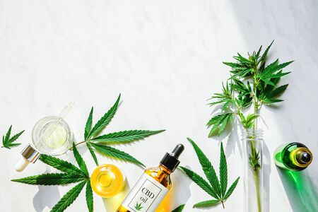 Various glass bottles with CBD oil, THC tincture and marijuana leaves on a marble background. Flat lay, minimalism. Cosmetics CBD oil