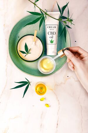 Pipette with CBD cosmetic oil in female hands on a table background with cosmetics, cream with cannabis and hemp leaves, marijuana. 版權商用圖片