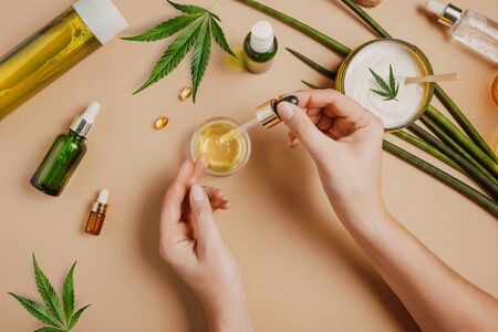 Pipette with CBD cosmetic oil in female hands on a table background with cosmetics, cream with cannabis and hemp leaves, marijuana 版權商用圖片
