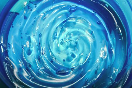 Hyaluronic acid cosmetic gel. Gel texture with bubbles on a blue background. Transparent smear of gel