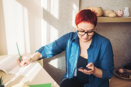 Business Woman with a smartphone writes in a notebook, places an order, keeps track of costs or online training. Home office concept, costing. Stay home, study and work online, quarantine coronavirus
