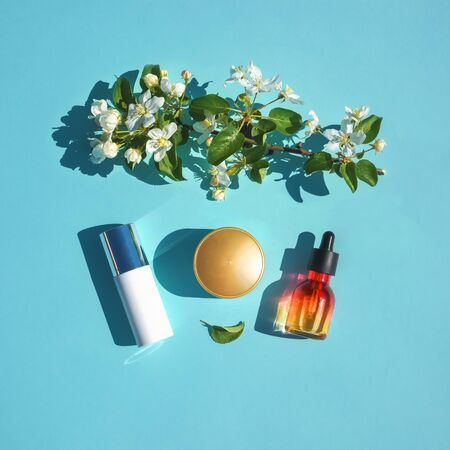 Set of beauty products flat lay on a blue background with flowers. The concept of natural cosmetics. Serum, cream skin care, minimal style