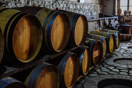 Vintage old oak barrels of wine, cognac in the wine dark vaults of the winery. Selective soft focus. Shooting in the dark