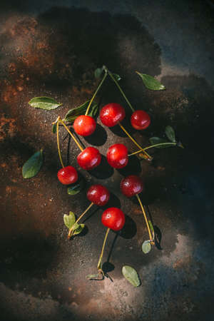 Ripe cherries with dew drops on a dark background in the rays of morning light. Cottagecore Aesthetics concept. Rustic, vintage style Juicy summer concep Stock fotó