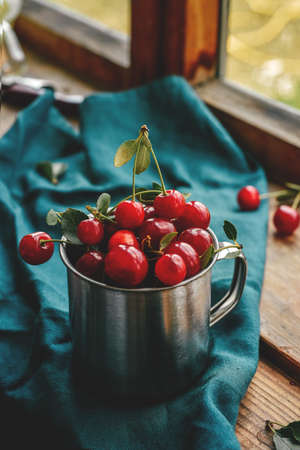 Ripe cherries in a mug. Good Morning Concept Cottagecore Aesthetics. Rustic, vintage style. Selective focus. Macro Harvest season concept