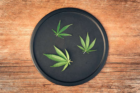 Cannabis leaves, mariuana of different sizes on a black round dish and a wooden table. Copy space, banner, flat lay Archivio Fotografico
