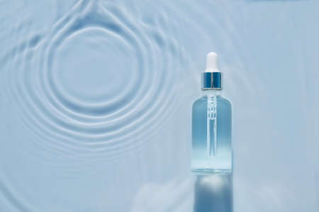 Cosmetic spa medical skin care, bottle for serum, micellar toner and emulsion on water texture background with splashes. Flat lay, copy space.