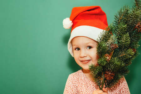 Little girl in a Santa cap with a fir tree smiles on a green wall background. Merry Christmas and New Year celebration concept. Holidays at home. Copy space