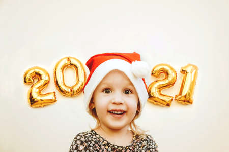 Little girl in Santa cap smiles against the background of golden numbers 2021. Concept of celebrating Merry Christmas and New Year.