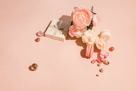 Monochrome floral composition with copy space in peach pastel color. Abstract background with flowers and a gift box in muted shades of patsel Minimal spring concept