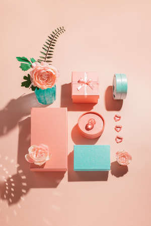Festive geometric arrangement of gift boxes and flowers in pastel colors with sunny shadows Congratulations on Womens Day and birthday. Romantic mockup concept for wedding invitation