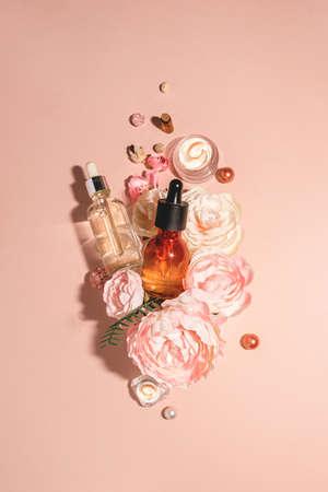 天然化妆品,生物血清和有机油,用于皮肤护理结合花卉。时髦单色淡色桃子背景。天然护肤和有机香水的概念