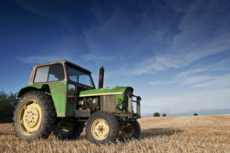 Green tractor in a harvested field