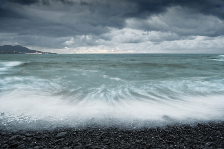 wather: A cloudy day in a rocky beach with the withe foam and the turcoise wather