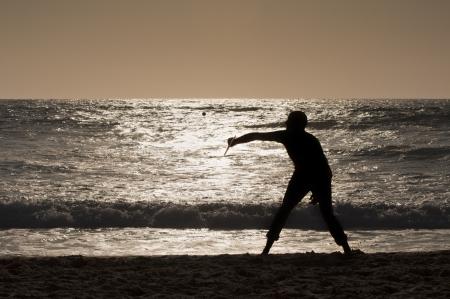Junge spielt mit Schl�ger bei Sonnenuntergang am Strand Lizenzfreie Bilder