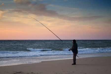 Man fishing in the beach shore at sunset