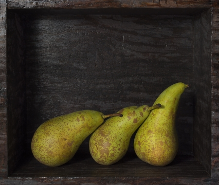 three green pears in a wooden box Stock Photo